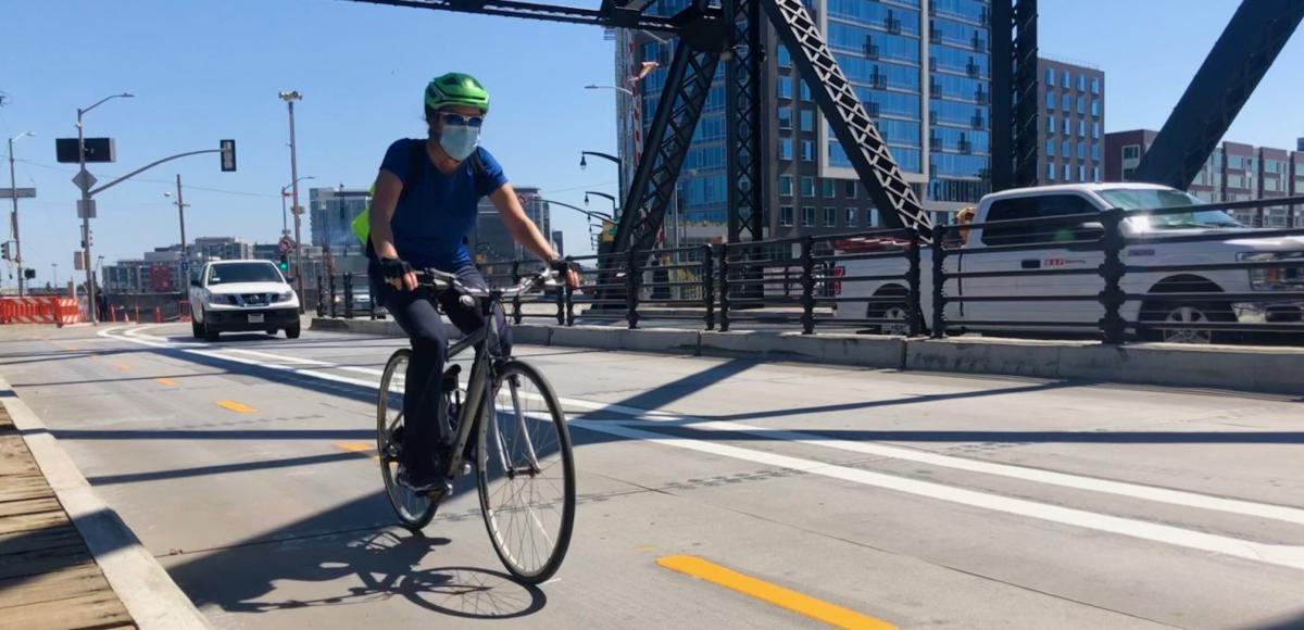 man biking over Third Street Bridge