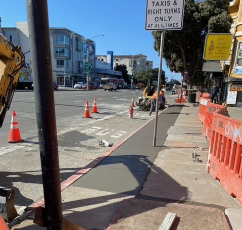 Crews restore the pavement after installation of new underground conduits at Commonwealth Avenue and Geary Boulevard
