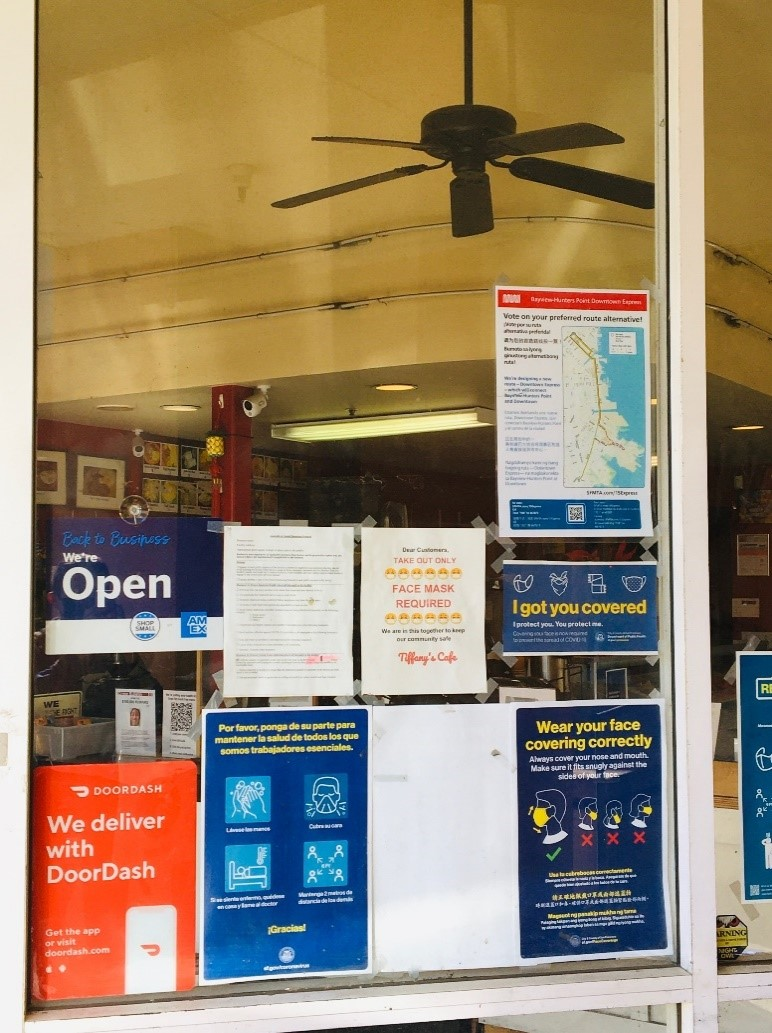 Photo of a storefront window, displaying the Bayview-Hunters Point Downtown Express Survey poster