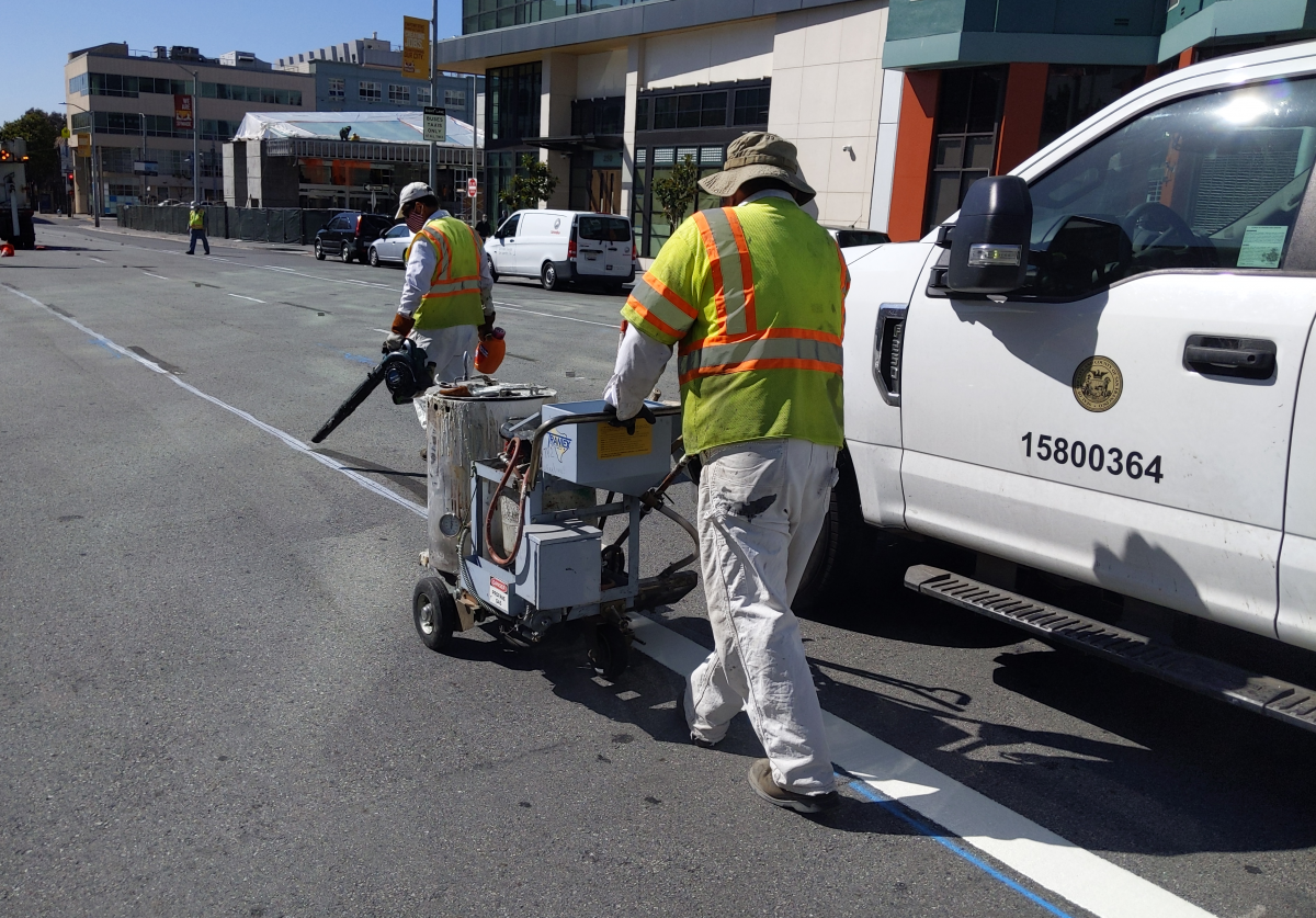 Work crews paint transit lane on 4th Street