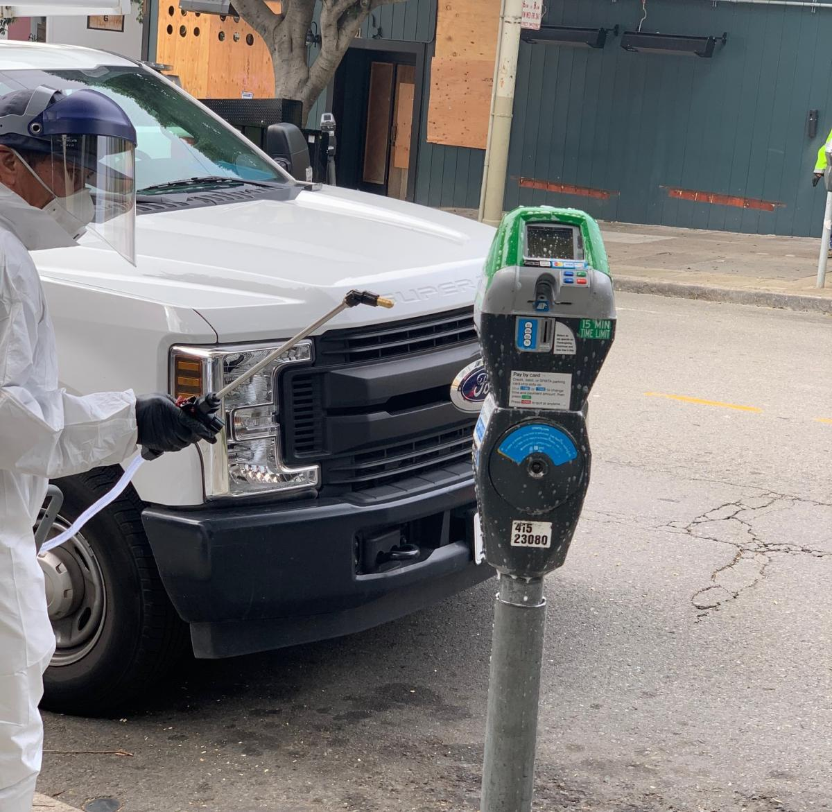 Parking Meter being sanitized by someone in a safety suit with visor