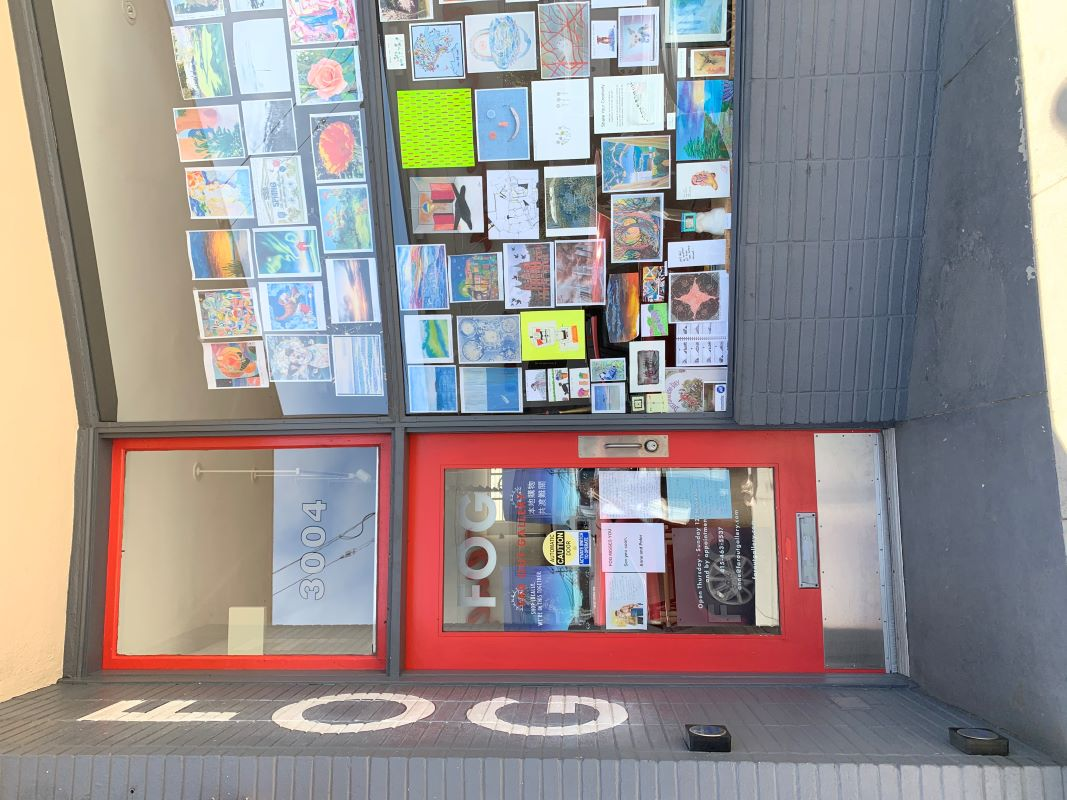 Picture of a store front with a large window filled with art work
