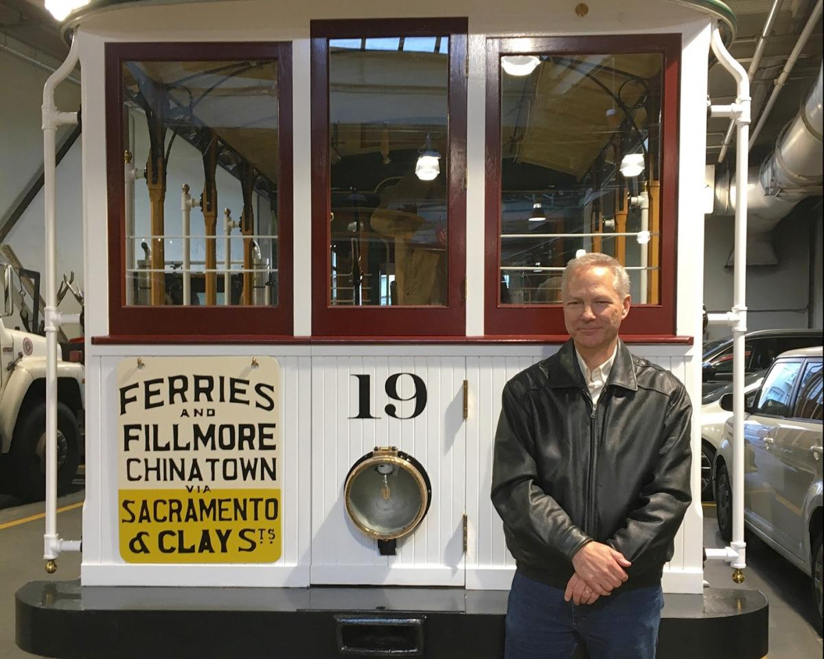 """Author Paul Bignardi poses with Sacramento-Clay Cable Car 19 """"Big 19"""" after its restoration in 2019."""