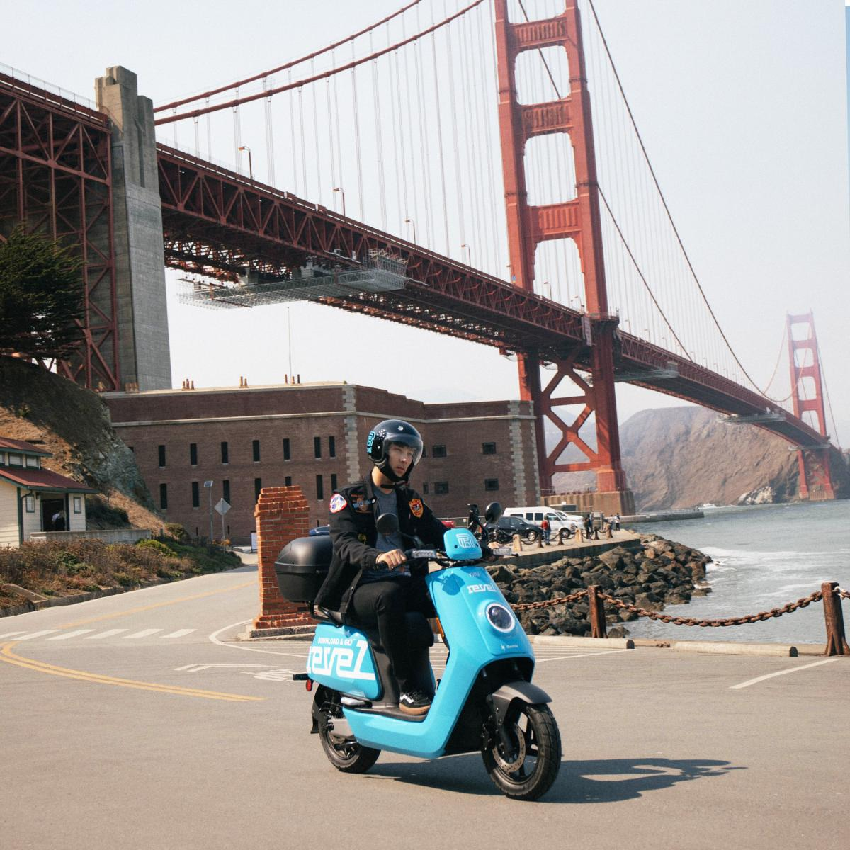 A Revel user rides a shared electric moped in front of Fort Point