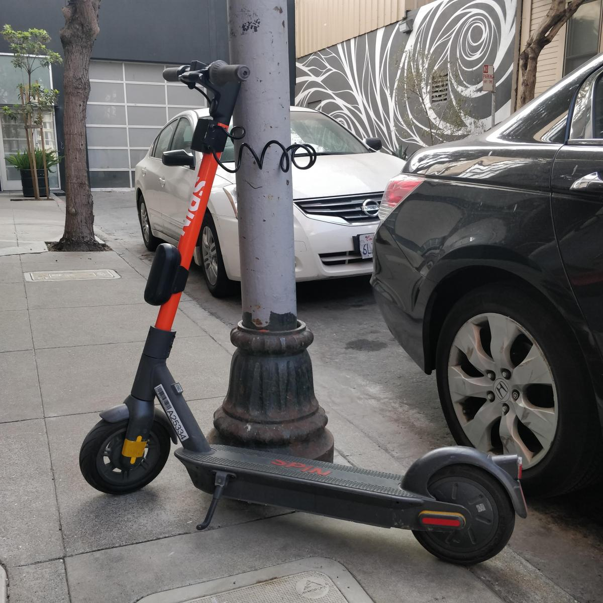 A Spin scooter parked with a lock-to device.