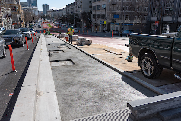 Looking south at crew member laying concrete between Eddy and Larch on Van Ness.