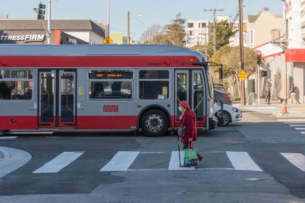 Photo: Geary Rapid bus and pedestrian traveling along Geary at Cook Street.