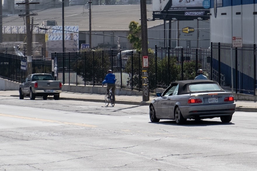 A person bicycling eastbound on Evans Avenue