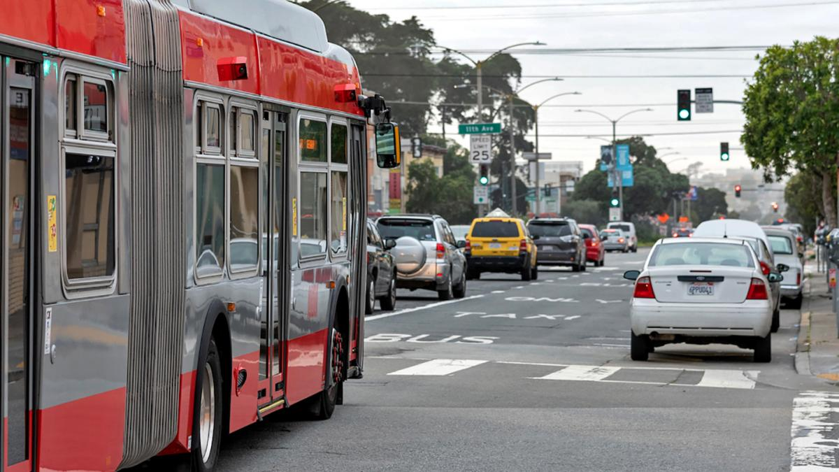 Photo of a bus in a transit lane in the Richmond district with traffic in the adjoining lane