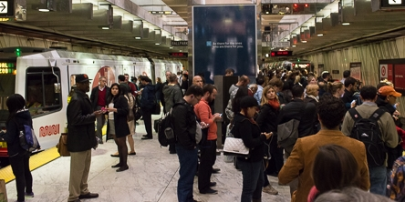 color photo showing Muni underground station platform filled with people.  To the left there is a Muni train waiting to board passengers and to the right is an empty trackway.