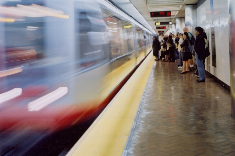 A view of a Muni Metro platform in 1999 with a train in motion on the left while passengers stand on the platform on the right.