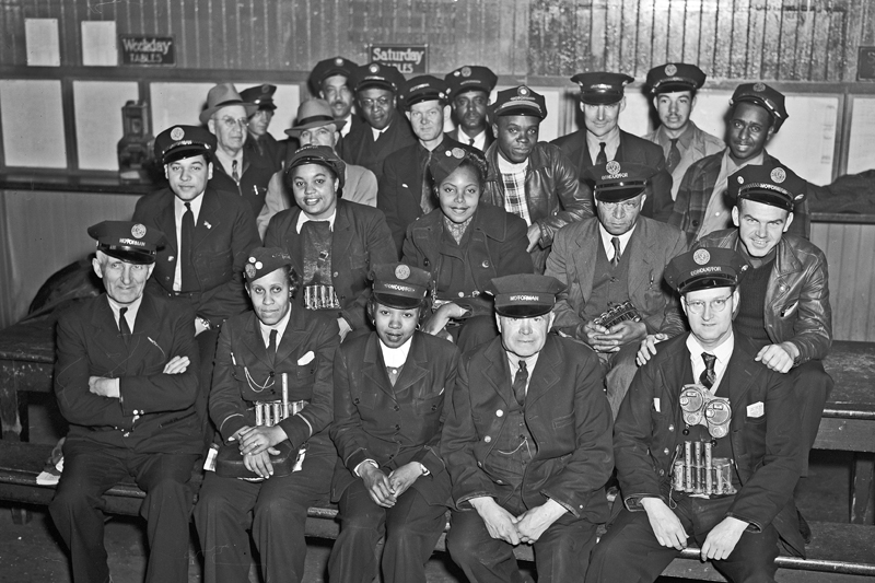 Black and white photo of a group of a male and female operators and conductors from a variety of racial backgrounds posing in four rows