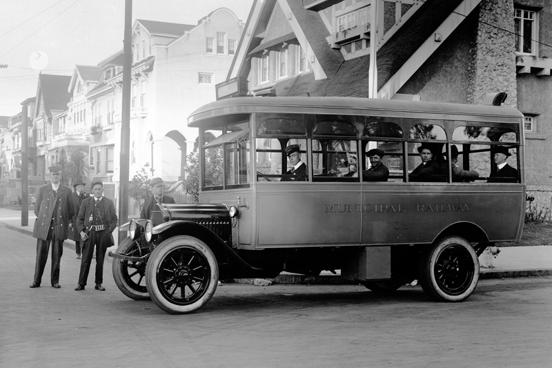 An early Municipal Railway bus at 10th Avenue and Fulton Street in 1917.  People are aboard the bus looking out the window towards the camera and two men stand in front of the bus.