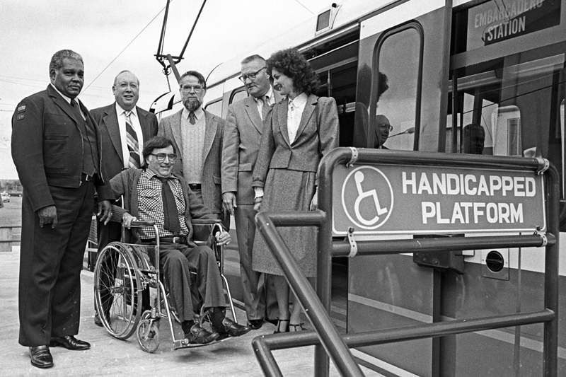 A man in a wheelchair is accompanied by a Muni operator and several others standing on a new Muni accessibility platform in 1983.