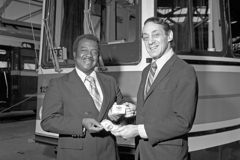 Muni General Manager Curtis Green and Supervisor Harvey Milk exchange paper money for a Muni fast pass with a light rail vehicle in the background.