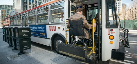 Passenger using a lift to enter a bus