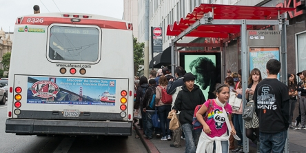color photo showing rear of muni bus stopped at bus stop with a large number of people crowding towards the rear doors and waiting at the stop and on the sidewalk.
