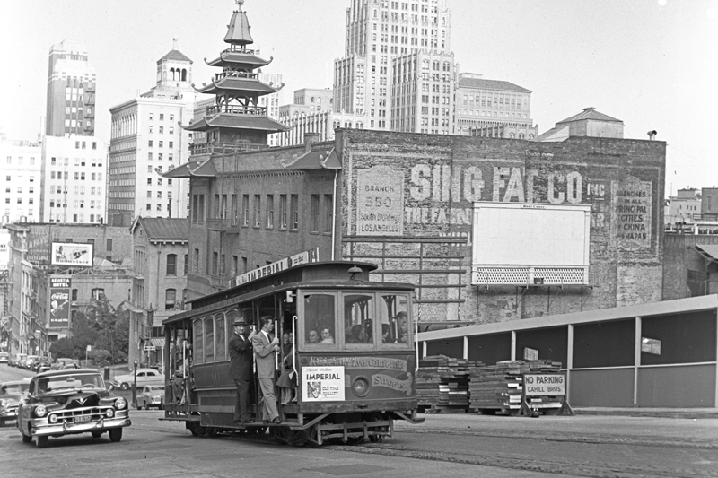 A cable car climbs the hill on California Street in 1951 with Chinatown and downtown skyline visible in the background.