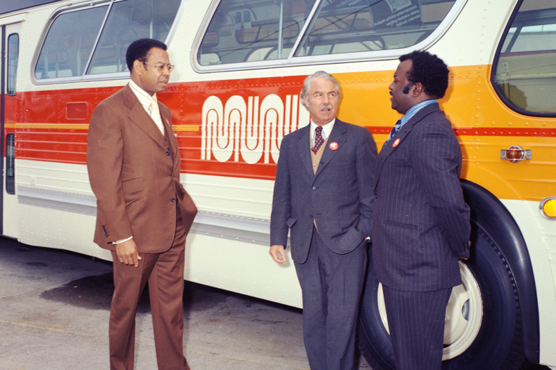 Three men standing alongside a Muni bus painted in new white, orange, and yellow colors in the 1970s