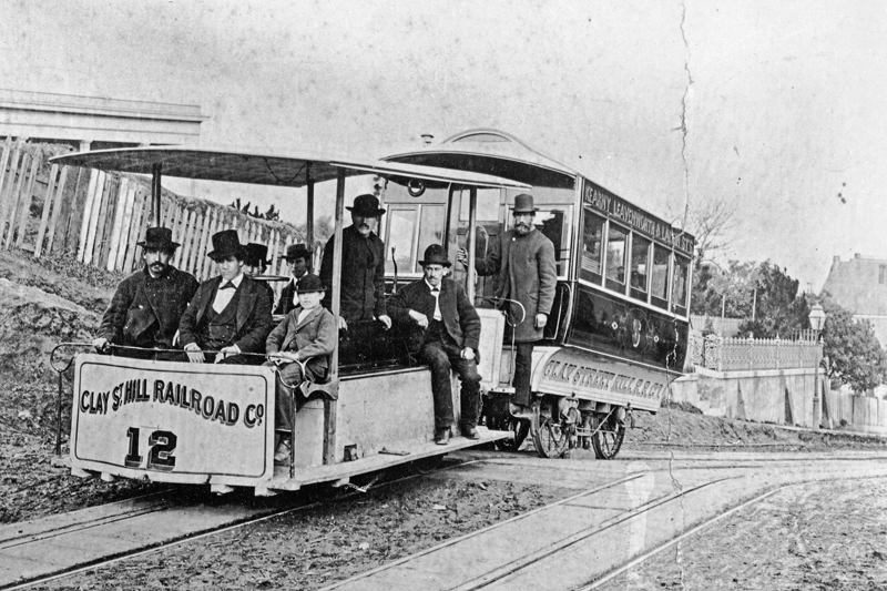 "A Clay Street cable train in 1873 with people on board. An open-sided car pulls an enclosed passenger ""trailer"""