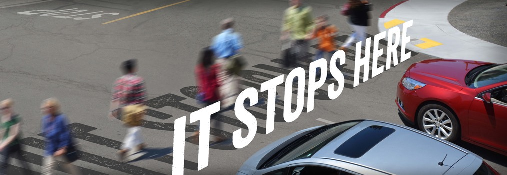 "Campaign ad image featuring the text ""It Stops Here"" and an intersection with cars next to pedestrians using a crosswalk."