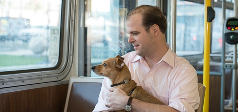 Customer and his leashed dog riding Muni