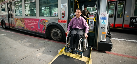 A passenger in a wheelchair uses a low-floor hybrid bus ramp