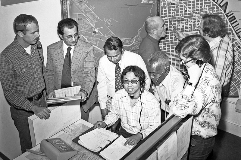 A group of Muni employees from the Muni Public Service Bureau cluster around a man with a headset inside the Muni Offices in 1977.