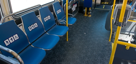 Interior of Muni coach showing blue colored priority seats near the front of the bus, seats are in a row at the left side of the image and have decals on them indicating their use.