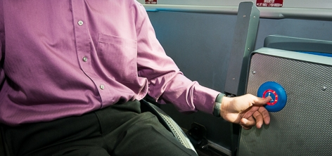 A passenger pushes the Accessible Stop Request button on a Hybrid Bus