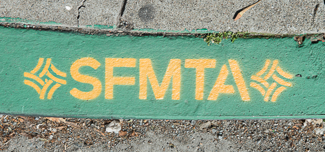 "Green Painted Curb with letters ""S,F,M,T,A"" in yellow paint."