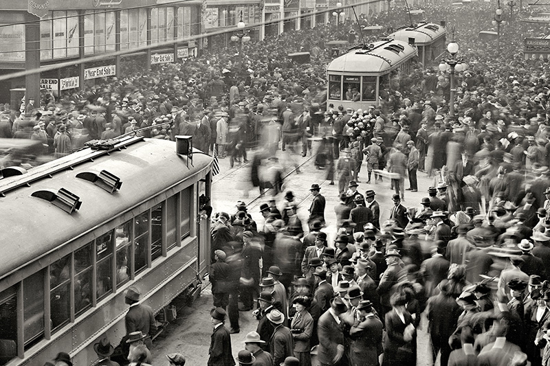 A large crowd gathers around two streetcars on Geary Street at Grant Avenue on December 28, 1912, to celebrate the opening day of the San Francisco Municipal Railway.