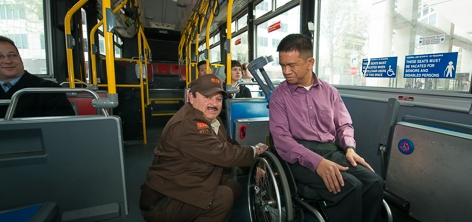 A Muni Operator secures a wheelchair passenger in a securement area