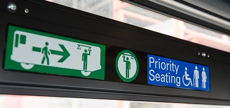 "detailed color photograph showing graphic decals on Muni bus. the decals, which are blue and white and green and white show stylized figures moving towards rear of stylized bus and have the words ""Priority Seating"" showing a wheelchair symbol."