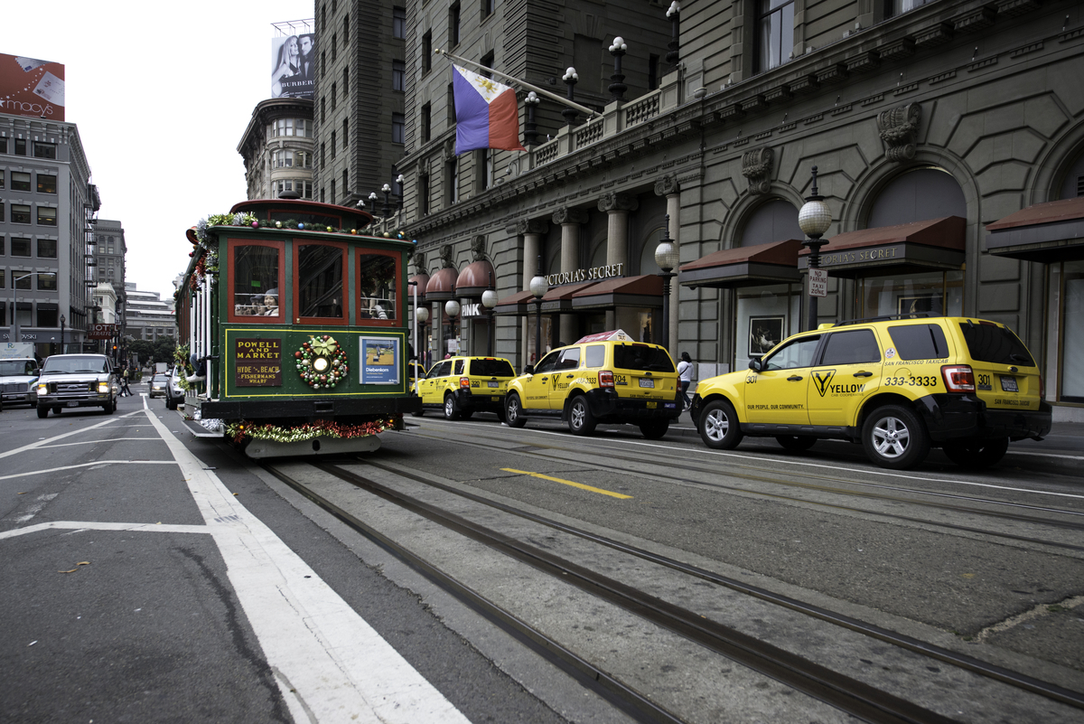 A decorated cable car travels north on Powell Street in front of the St. Francis hotel.