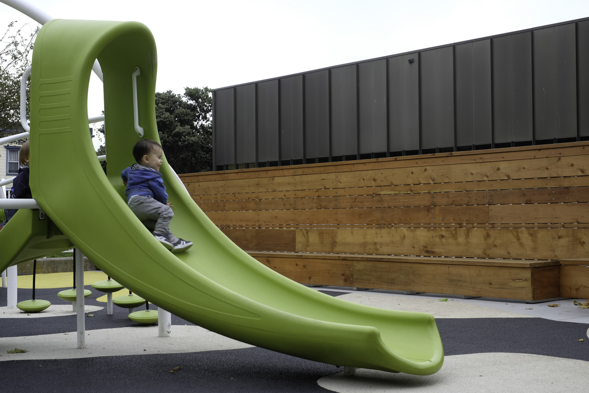 Smiling child going down a green slide in a playground
