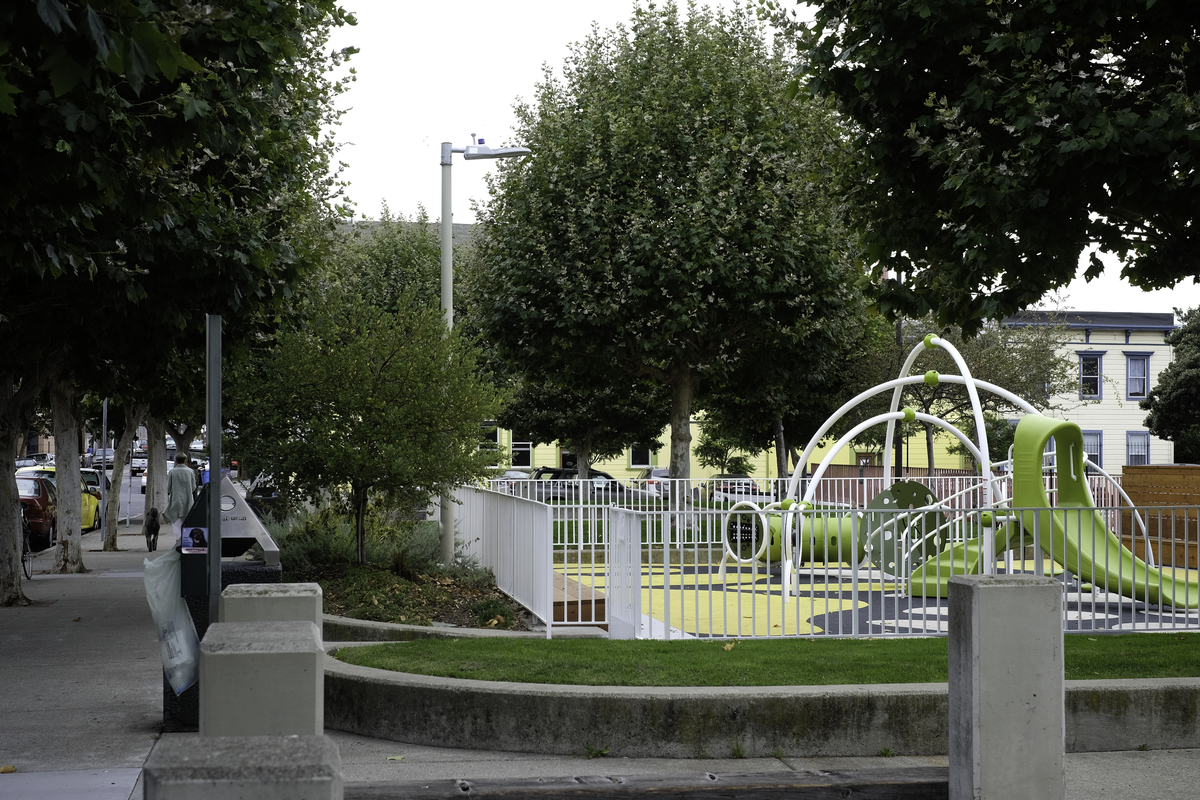 Children's green and white play equipment in a fenced-in playground on a tree-lined street.