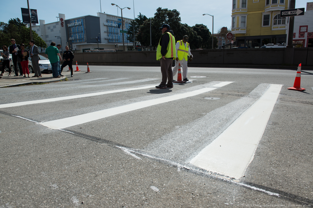 Zebra-striped crosswalk being installed at Emerson and Geary.