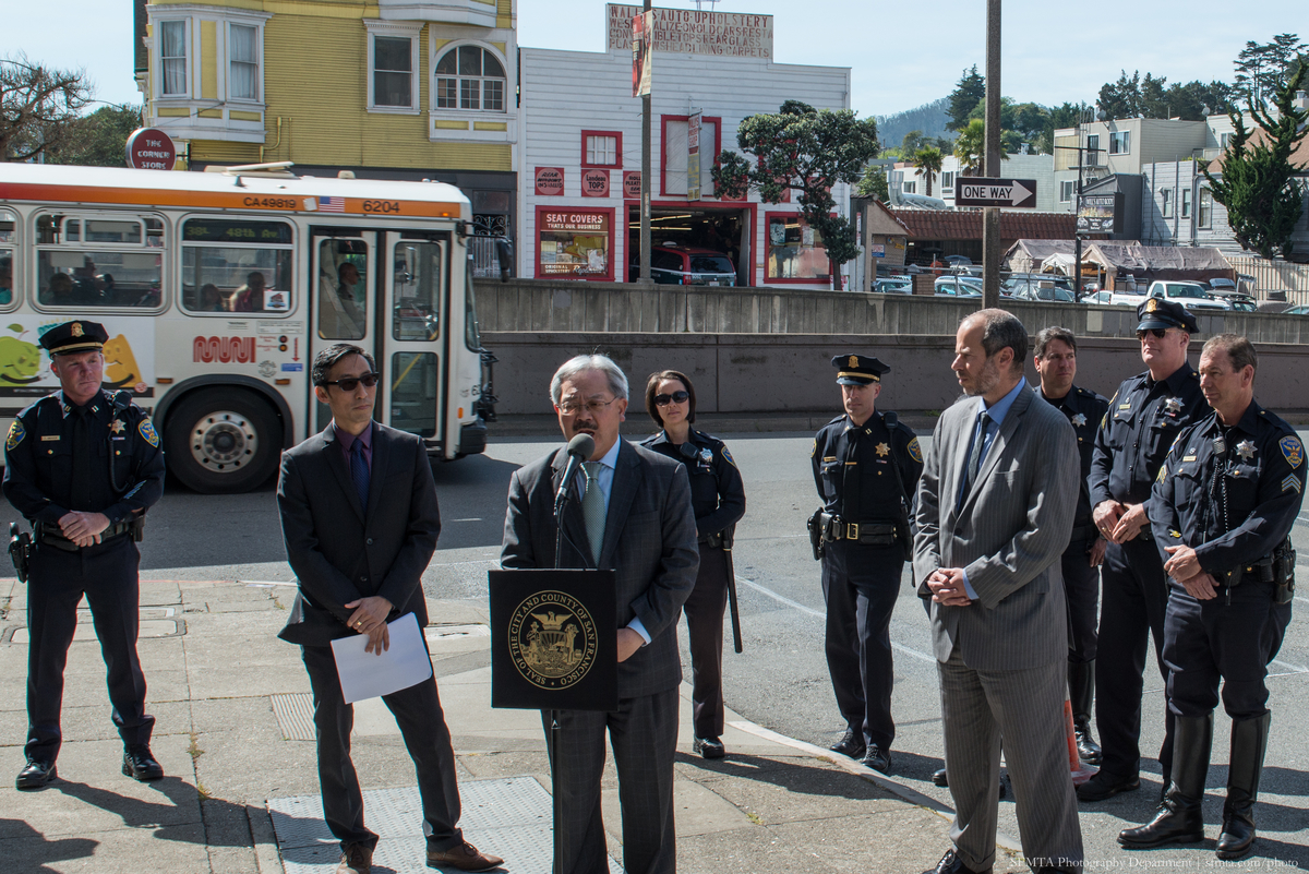 Mayor Lee speaks while Ed Reiskin, Supervisor Mar and uniformed police officers stand on corner of Geary and Emerson with 38 Geary bus passng in the background.