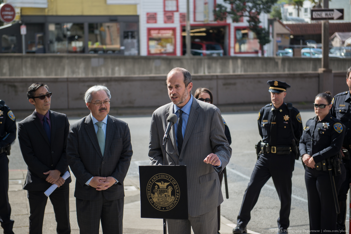 Mayor Lee, Supervisor Mar and uniformed police officers stand while Ed Reiskin speaks on Geary Blvd. for press conference