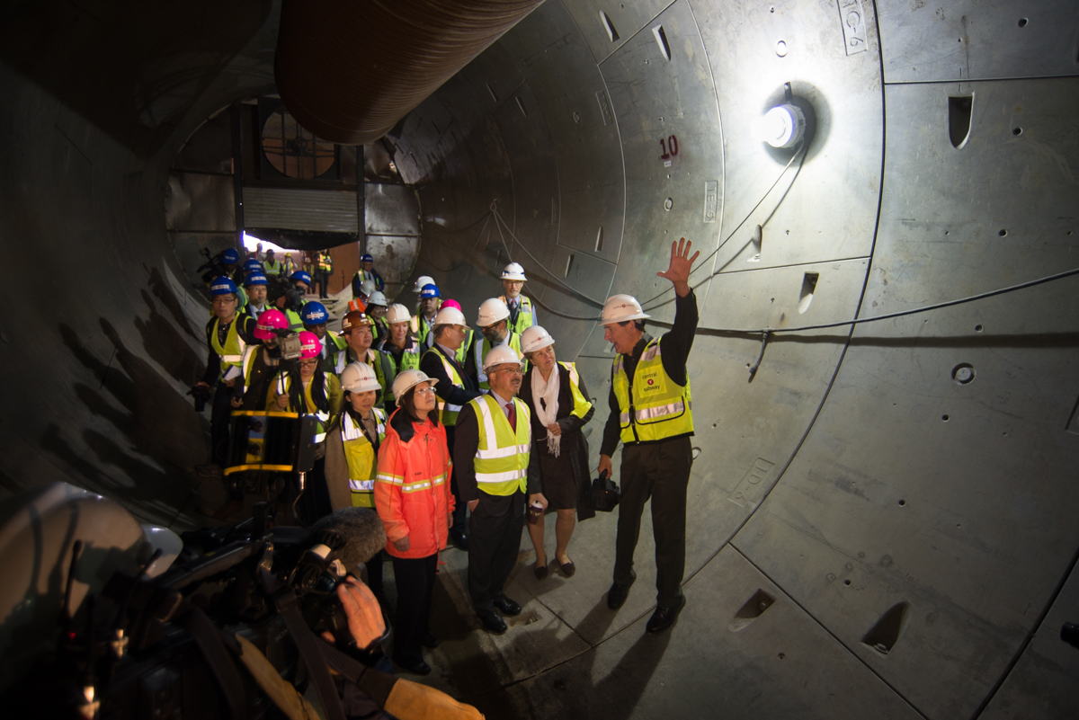 Mayor Lee, project director John Funghi, additional staff, and membrs of the media stand in the concrete tunnel.