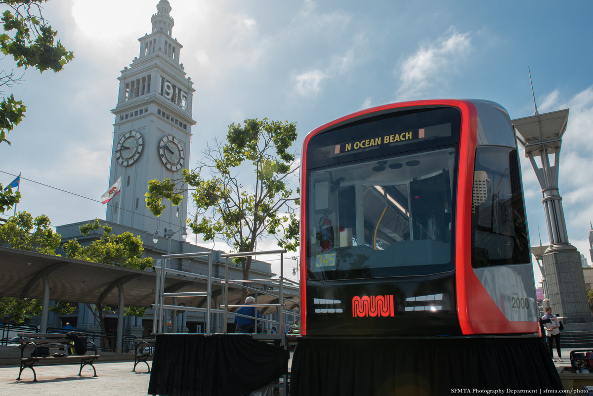 Mock-up of new Muni light rail vehicle on plaza along F Line on Embarcadero with Ferry Building in the background
