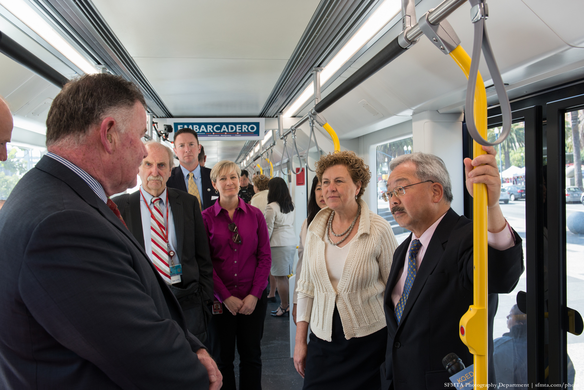 Four men and three women stand on a group inside the LRV mock-up.