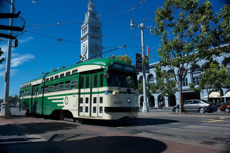 Green and cream historic streetcar in front of the Ferry Building on The Embarcadero.