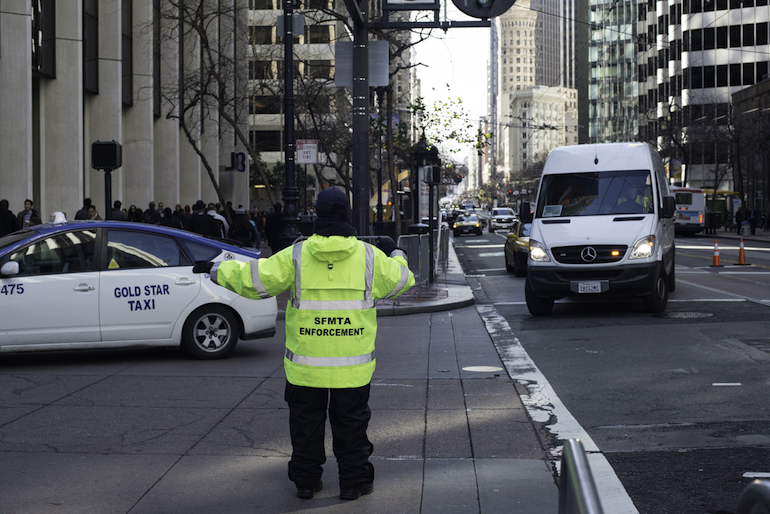A parking control officer stands on Market Street in yellow cold-weather reflective gear, directing a taxi and delivery truck.