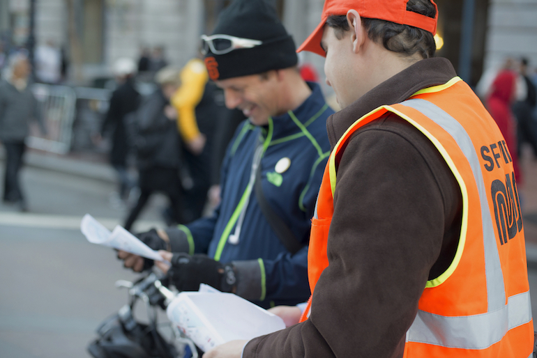 A Muni ambassador in safety orange vest and cap directs a visitor to SF during Super Bowl City.