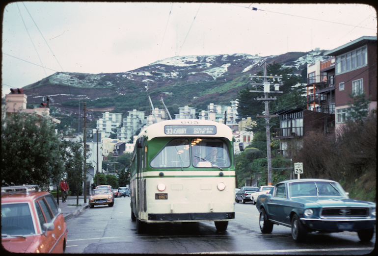 a color photograph from February 1976 showing a Muni electric trolley coach operating on the 33 Ashbury line on Clayton Street near Deming Street.  the bus and a 1960s model Ford Mustang car are in the mid ground and Twin Peaks, dusted with white snow is seen in the background.