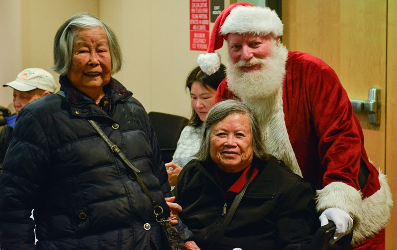 Santa Claus stands next to two women attending the Cable Car Seniors Luncheon.