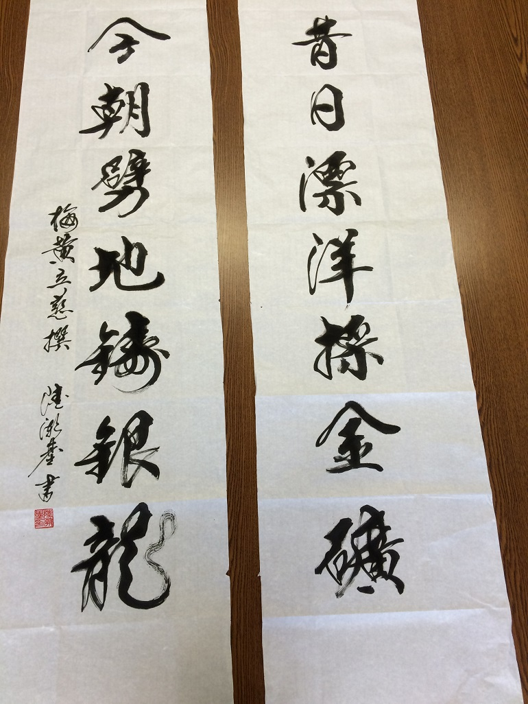 Black Chinese calligraphy painted on two wide strips of cloth.