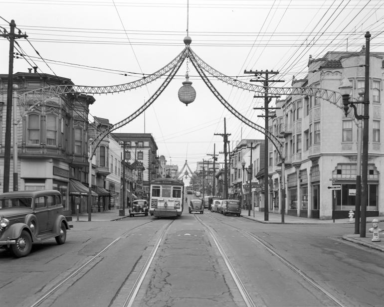 Looking north on Fillmore and Sutter streets at streetcar and ironwork arches above intersections.